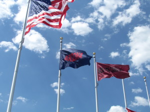 Team flags fly on flagpoles near the stadium. As each team is eliminated, their flag is removed.