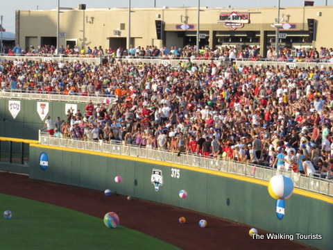 CWS fans have a tradition of playing with beach balls in the outfield seats. They tend to find their way on the field. Ground crew members gather them up.