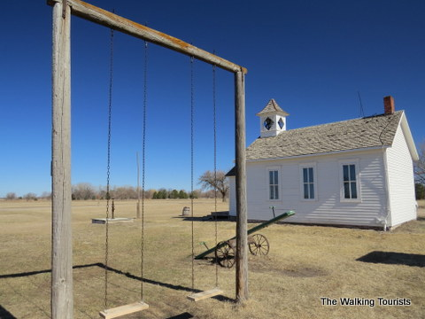 An old schoolhouse with swing set and Teeter Totter at Stuhr Museum