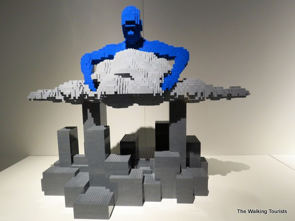 man holding gray cloud over the city with lego pieces