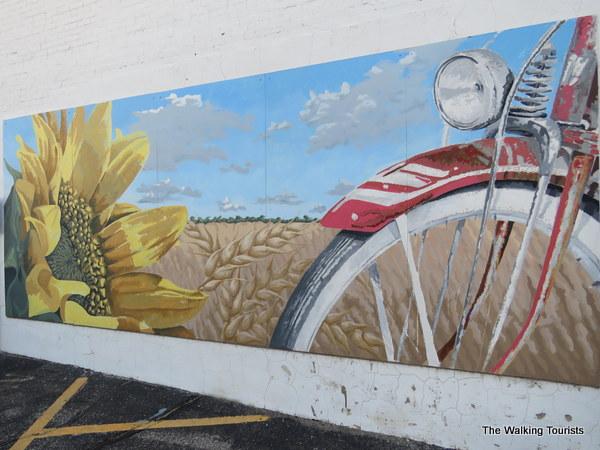 Mural featuring a bike near a sunflower field