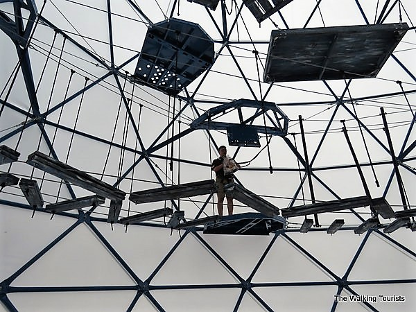 A staff member stands on the second level of obstacles inside the Challenge Dome.