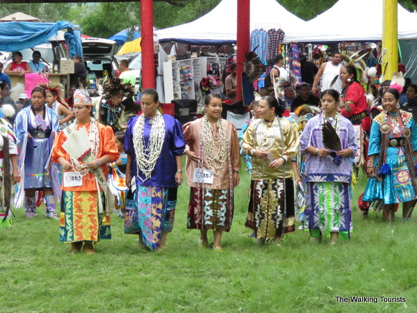 Women in colorful regalia slowly dancing at powwow