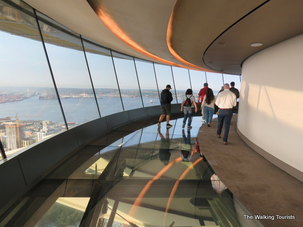 Visitors walk along the glass floor on the rotating floor of the Space Needle