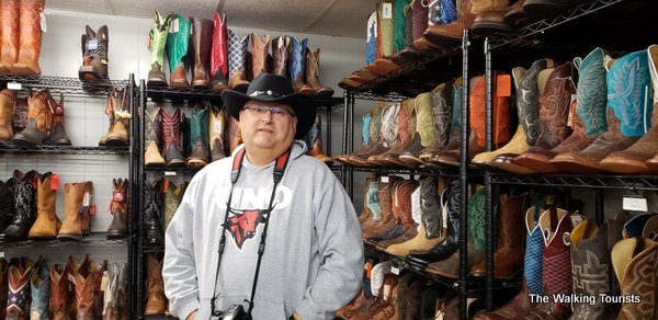 Tim wearing a cowboy hat and standing in front of boots.