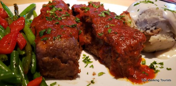 The meatloaf dinner features a tomato sauce topping, fresh mashed potatoes and green beans.