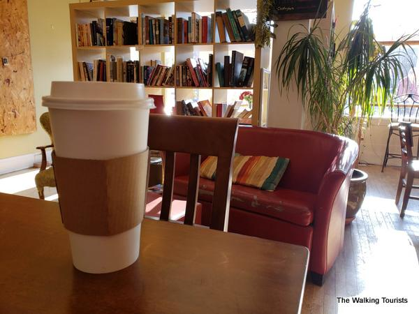 Coffee in a plastic cup in front of a book shelf.