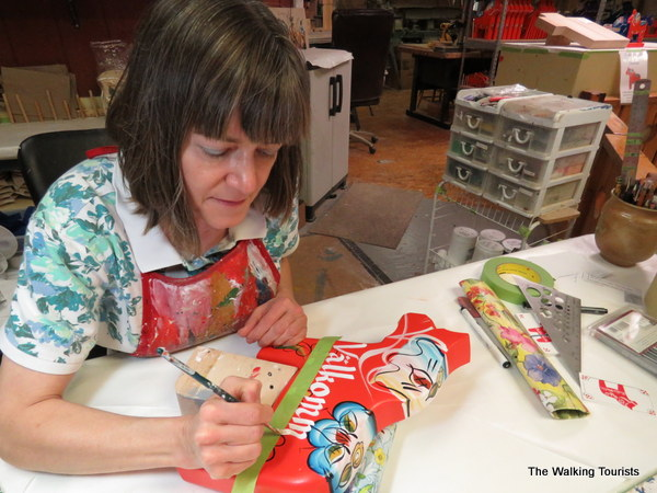 "Julie Holk paints ""Valkommen"" on a dala horse figure."