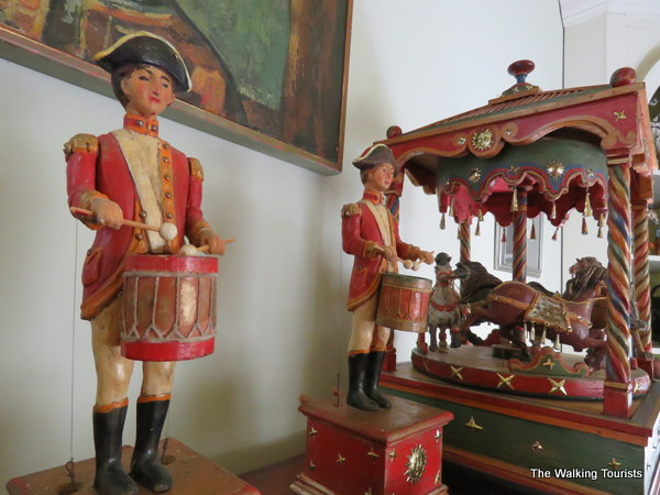 Handcarved toy soldiers playing drums next to a carousel