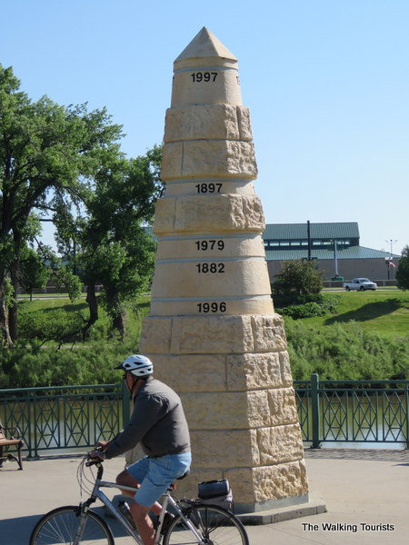 A bicyclist enjoys a nice summer day as he cruises past a monument noting the city's flood history.