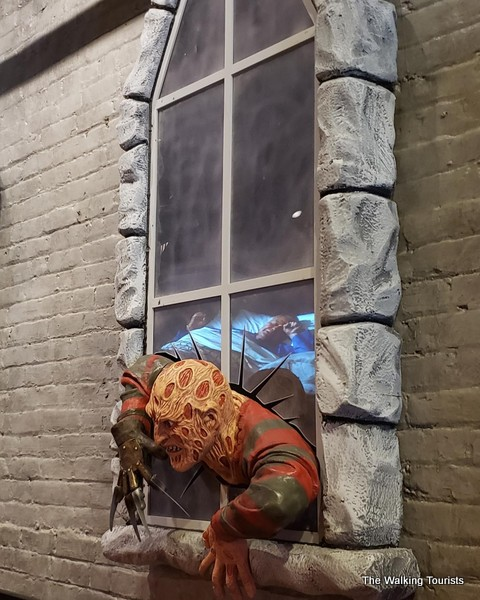 Freddie Krueger appears to be climbing out of a window above a booth.